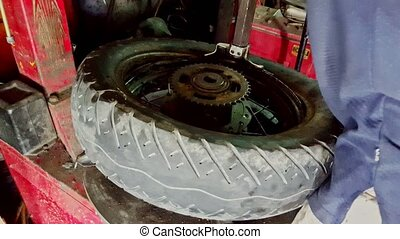 Closeup Man Installs Tire on Balance Machine in Shop -...
