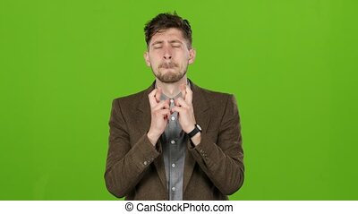 Businessman crosses his fingers on both hands in the hope of success. Green screen