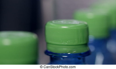 Green caps on plastic bottles close up. - Green caps on...