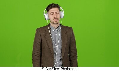 Boy businessman listens to quiet music in headphones. Green...