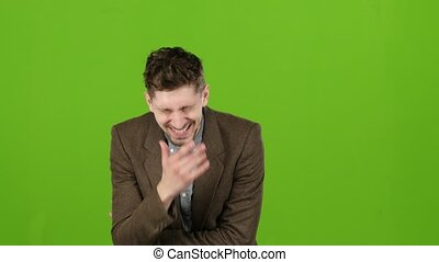 Businessman stands and smiles, a joke makes him laugh. Green...
