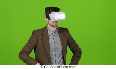 Boy in virtual glasses looks at imaginary photographs and...