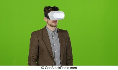 Guy in 3d glasses looks at the graphics and virtual...