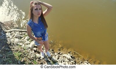 Girl on the river bank. Woman lifestyle stand by nature the...
