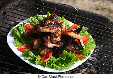 chicken legs on the grill with vegetables