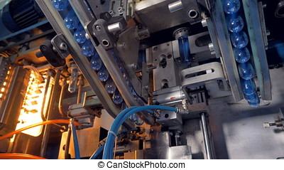 Plant machinery processing PET tubes to make bottles. - The...