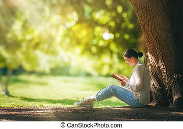 woman reading a book - Young woman reading a book under big...