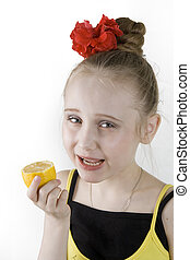 Girl eating an lemon - A little cute girl eating an lemon