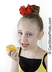 Girl eating an lemon - A little cute girl eating an lemon