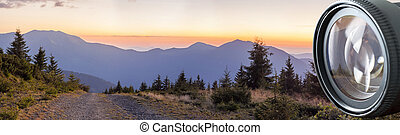 Panorama of sunset in Carpathian mountains with a gravel road in front in digital photo camera lens reflection