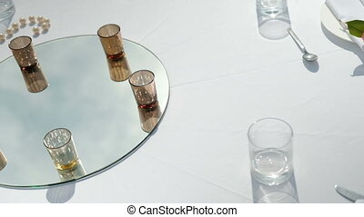 white table with drinks on mirror for banquet on fresh air...