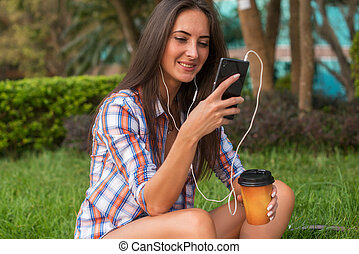 Attractive young woman in headphones listening to music...