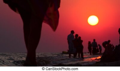 Evening walk along the coast. Silhouettes at sunset. A group...