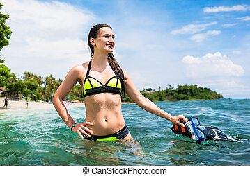 woman holding snorkelling equipment, standing in sea -...