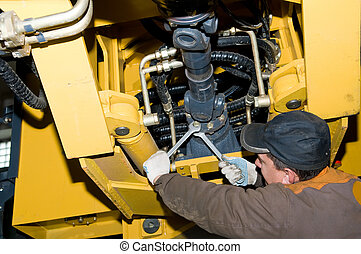 maintenance work of heavy loader - repairman worker screwing...