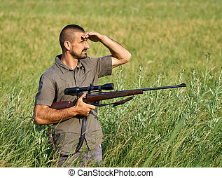 Gamekeeper with a rifle in a field - Wildlife gamekeeper or...