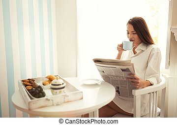 Beautiful woman reading morning paper and drinking coffee