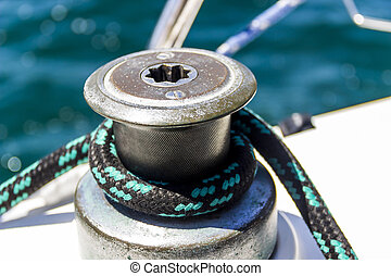 the yacht winch and rope - close-up of sailboat winch and...