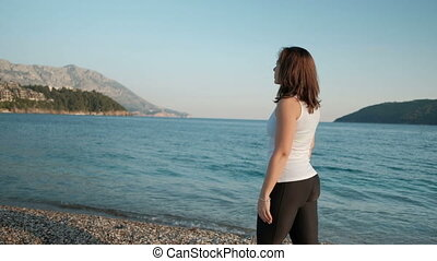 woman walking on lake shore nature on background looking...