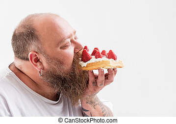 Relaxed male fatso eating tasty cake - Cheerful bearded fat...