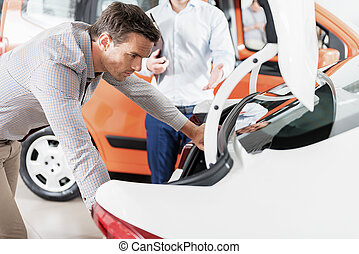 Serene man watching at automobile trunk