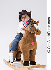 Little Caucasian Girl in Cowgirl Clothing On Symbolic Horse...