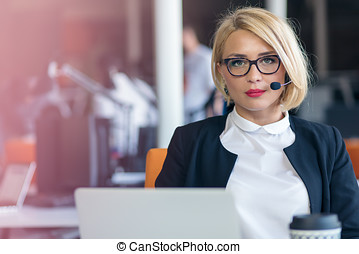 Customer service representative at work. Beautiful young woman in headset working at the computer