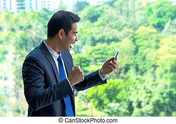 Businessman arms up and seeing good news on mobile phone at office