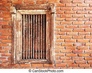 antique wooden window with iron bars on brick wall