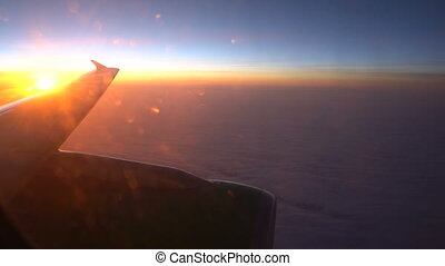 Wing of an airplane in the sunrise, view from the window