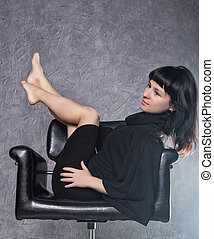 beautiful fashionable lady wearing a gothic black dress with high collar, poses in white smoke on a leather armchair