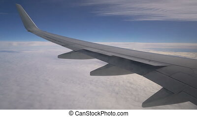 Wing of an airplane above the clouds, view from the window