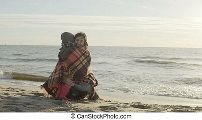 Cute little boy and his mother on shore of sea. Woman with...