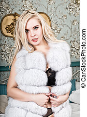 beautiful young woman in lingerie and white fur coat posing on a bedroom background