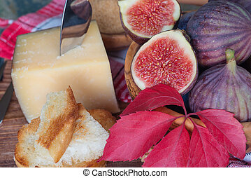 Autumn Still Life - Ripe figs in a wooden bowl, cheese, cane...