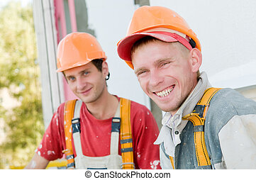 two builder facade painters - Two happy smiling builder...