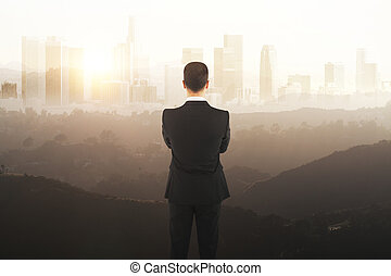 Man looking at brown landscape - Back view of thoughtful...