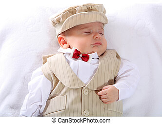 A portrait of a newborn baby boy in a blessing outfit.