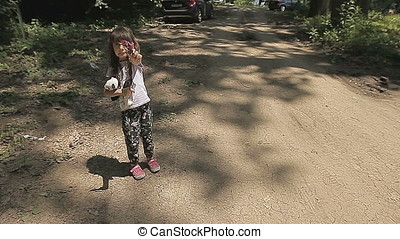 Little Girl in Forest Showing Puppet - Little girl in forest...