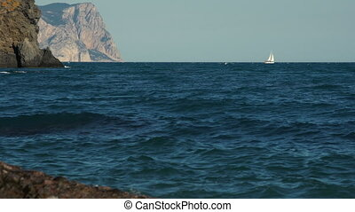 Sea coast with high rocks and a white sailboat in the sea