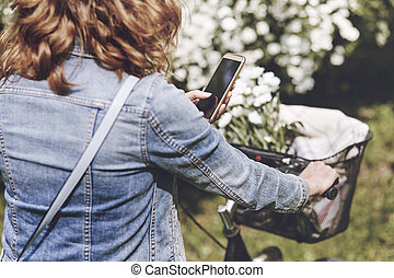 Woman using the mobile phone during the cycling