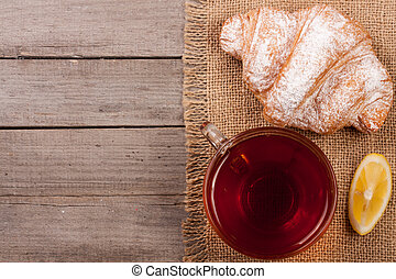 croissant with a cup of tea on an old wooden background with copy space for your text. Top view
