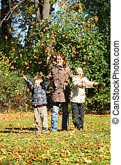 Mothers and children in autumn park.