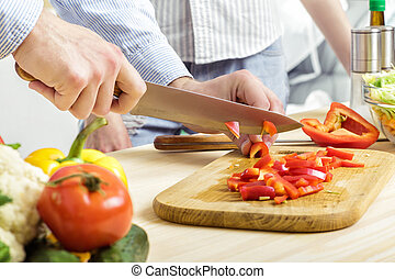 Hands of man chopped red bell pepper on board. Couple chopping vegetables in kitchen