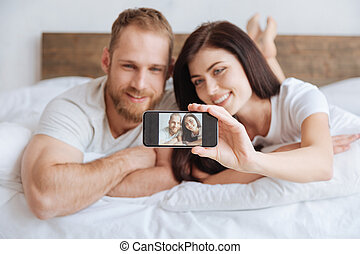 Portrait of newly married couple taking selfie in bed -...