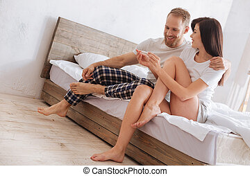 Millennial woman showing pregnancy test results to her husband