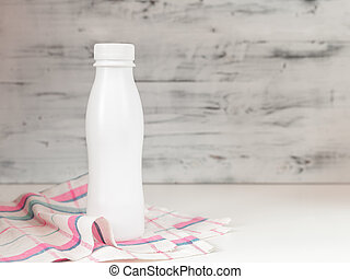 White blank plastic bottle with screw cap on kitchen table