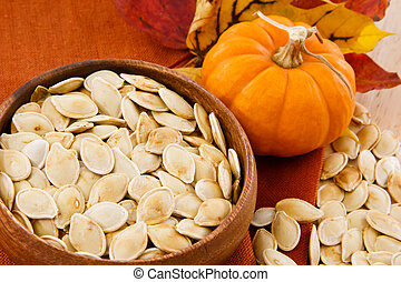 Close up of healthy pumpkin seeds and pumpkin against...