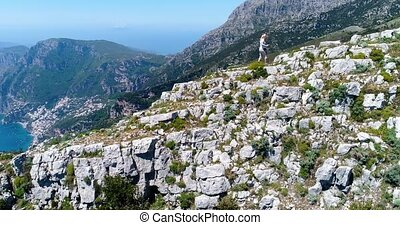 Young woman hiking in mountains above Amalfi coast in Italy