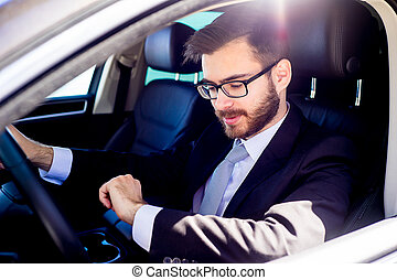 Businessman checking time in car - Portrait of a handsome...